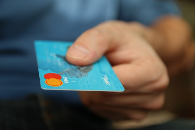 person holding out a blue debit card